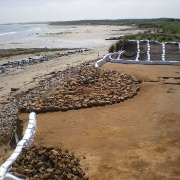 The half-eroded Bronze Age burial cairn once exposed and cleaned of loose sand.