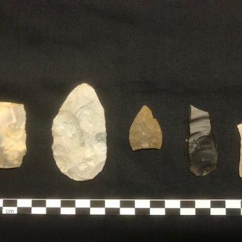 Neolithic flint tools found within the kettle hole, from left to right: a broken blade, a retouched burnt knife, a leaf-shaped arrowhead, a blade tool and a broken blade (scale = 20cm). © Copyright ARS Ltd