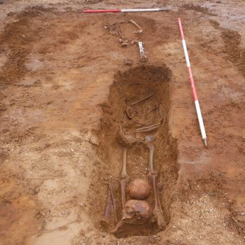Decapitation burial with two skulls between legs