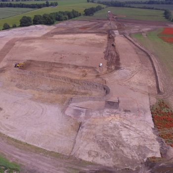 A view of the site with one of the wetland areas surrounded by orange fencing in the foreground and our team excavating to the left of the white van. Can you spot the two enclosures in the top left of the photo?