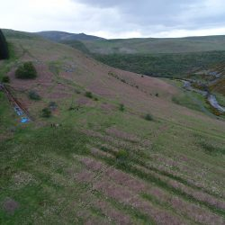A view of the site within the Breamish Valley. Note the trench running down through the terraces and pointing towards later medieval ridge and furrow remains.