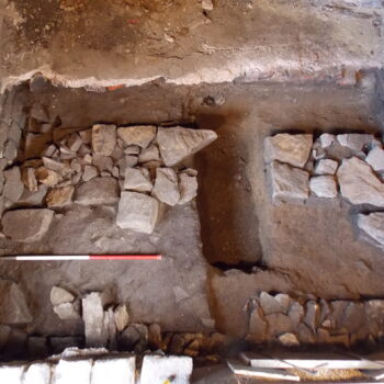 The substantial wall foundations of the previous building found within Trench 2 (scale = 1m). © Copyright ARS Ltd 2021
